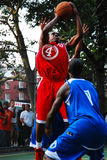 Taking a shot. A basketball player makes his move and shoots over his defender at a game in Greenwich Village, New York Stock Images