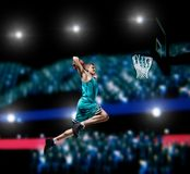 Basketball player making slam dunk on basketball arena. Lights background stock photo