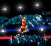 Basketball player making slam dunk on basketball arena. Lights background royalty free stock image