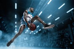 Basketball player on big professional arena during the game. Basketball player making slam dunk. Basketball player in motion or movement on big professional royalty free stock image