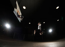 Basketball player at night. Jumping and aiming at hoop with lights on Royalty Free Stock Photos