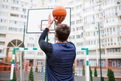 A basketball player at an outdoor stadium trains, throwing a ball into the ring, lifting his hands up. Basketball player in an open autumn stadium, training stock image