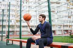 A basketball player in an open stadium holds the ball on his fingers. Royalty Free Stock Photos