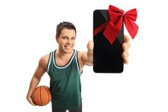 Basketball player showing a phone wrapped with a red ribbon as a Royalty Free Stock Photos