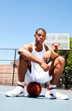 Basketball player sitting on ball Royalty Free Stock Photography