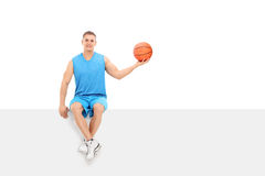 Basketball player sitting on a blank billboard Royalty Free Stock Photo