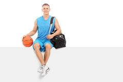 Basketball player sitting on a blank panel Royalty Free Stock Photos