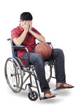 Basketball player sitting on wheelchair with ball Stock Images