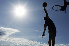 Basketball player slam dunk silhouette. A silhouette of a basketball player in mid air about to slam dunk with the sun behind him creating a flare effect royalty free stock photos