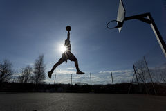 Basketball player slam dunk silhouette. A silhouette of a basketball player in mid air about to slam dunk with the sun behind him creating a flare effect Stock Photo