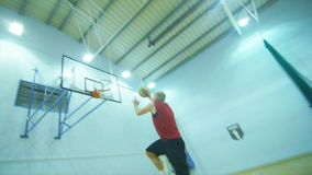 Basketball player slam dunking in slow motion indoors stock footage