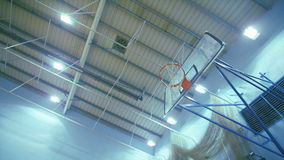 Basketball player slam dunking in slow motion indoors stock video