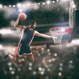 Acrobatic slam dunk of a basket player in the basket at the stadium. Basketball player slams dunk the ball to the basket stock photos