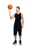 Basketball player spinning ball on his finger. Full length portrait of a handsome basketball player spinning ball on his finger isolated on a white background Royalty Free Stock Image