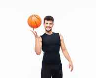 Basketball player spinning ball on his finger. Smiling basketball player spinning ball on his finger isolated on a white background and looking at camera Royalty Free Stock Image