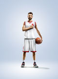 Basketball player is spinning on his finger. Basketball player in action isolated on white Royalty Free Stock Images