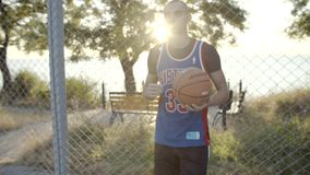 Basketball player stands with the ball on the court, waiting for the game. In slow motion. The best player portrait stock footage