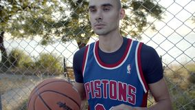 Basketball player stands with the ball on the court, waiting for the game. In slow motion. The best player portrait stock video footage