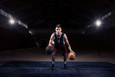 Basketball player Stationary Double Dribble. One young man only, one basketball player, Stationary Double Dribble, two balls, two hands, dark indoors court royalty free stock image
