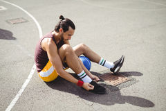 Basketball player tying shoe laces while sitting Royalty Free Stock Images