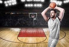 Basketball Player on a white uniform in basketball court Royalty Free Stock Photos
