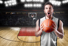 Basketball Player on a white uniform in basketball court Stock Photos