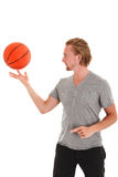 Basketball player. Young attractive basketball player wearing a grey tshirt with black shorts, holding a basketball. White background Royalty Free Stock Photos