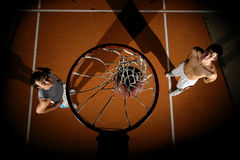Basketball players. Two mans is playing basketball in dark picture above basket Stock Photos