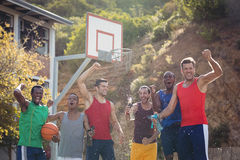 Basketball players celebrating by splashing water on each other. In basketball court outdoors Royalty Free Stock Photos