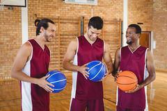 Basketball players interacting with each other in the court Stock Images