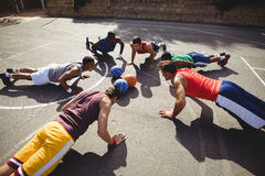 Basketball players performing push up exercise Royalty Free Stock Photos