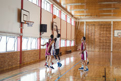 Basketball players playing basketball in the court. Indoors Stock Photo