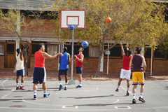 Basketball players practicing in basketball court. Outdoors Stock Photo