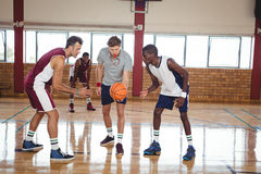 Basketball players ready for the jump ball. In the court indoors Royalty Free Stock Photo