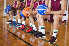 Basketball players sitting on bench with basketball. In the court Stock Photo
