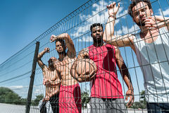 Basketball players standing near net on court. Multicultural group of basketball players standing near net on court Royalty Free Stock Photography