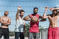 Basketball players standing near net on court. Multicultural group of basketball players standing near net on court Stock Photos