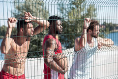 Basketball players standing near net at court. Multiethnic group of basketball players standing near net at court Royalty Free Stock Photography