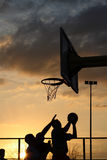 Basketball players at the sunset. Silhouettes of basketball players at the sunset Royalty Free Stock Photos