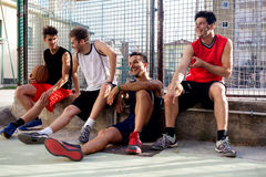 Basketball players take a break sitting on a low wall Royalty Free Stock Photography