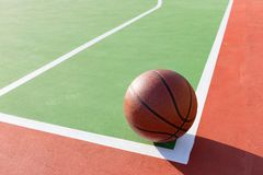 Basketball on the playing field near the corner. In a day time Royalty Free Stock Image