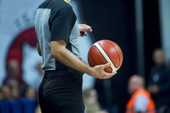 Basketball referee holding a basketball at a game in a crowded sports arena stock images