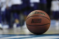 Basketball rests on court. CHARLOTTE, NC: A gameball rests along the baseline prior to the 2018 NCAA men`s basketball tournament Stock Image
