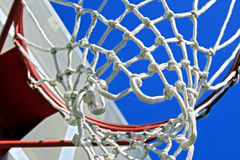 Basketball Rim and Net. Red basketball rim and white net with blue sky above Stock Image