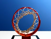 Basketball rim seen from below against clear blue sky. Basketball rim hoop seen from below against clear blue sky Stock Images