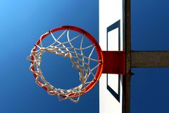 Basketball rim seen from below against clear blue sky Stock Image