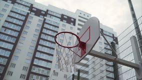 Basketball ring in the courtyard of a multi-storey building. A new basketball ring with a net. Basketball hoop is made of orange steel with. basketball ring in stock video footage