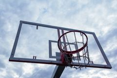 Basketball ring with a metal mesh with a transparent shield against a background of thick clouds. stock photo