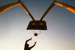 Basketball's silhouette. Man jumping with the ball Stock Photos