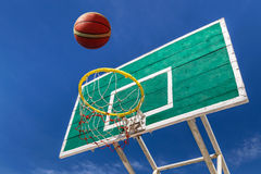 Basketball scoring goal on hoop. With blue sky background royalty free stock image